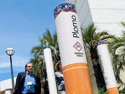 Uruguayan health minister Daniel Olesker walks through an installation of enlarged model cigarettes.
