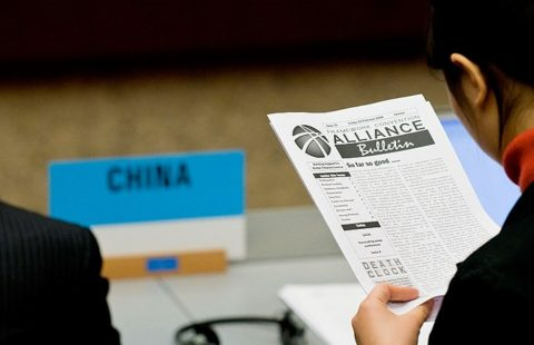 A delegate from China reads the Bulletin